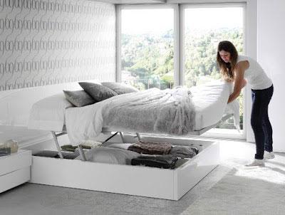 Cómo elegir somier. Canapé de la colección Slaap de Kibuc. Composición de dormitorio formada por cabezal Ola con luz Led, aro de cama abatible y elevable, y mesitas Diagonal con 2 cajones. Disponible en otras composiciones y acabado